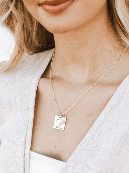A sterling silver square with a small sterling heart fused on top, hand-stamped with a name or message