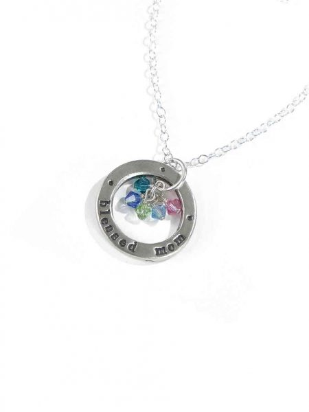 "A sterling silver circle hand stamped with ""blessed mom"" along with kids birthstones. Perfect gift for a mom"