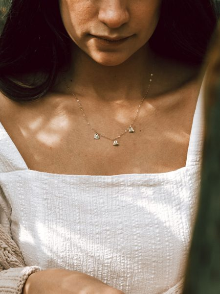 Dainty gold heart necklace with engraved initials. Customize it with the number of hearts. Perfect for mom, grand mom, wife