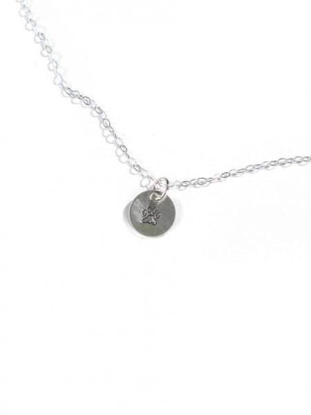 A beautiful hand-stamped sterling silver circle with the cutest little paw makes the best gift for a crazy dog lover.