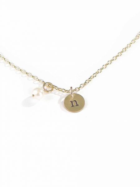 A personalized jewelry piece with hand stamped initial on the dainty gold-filled disc