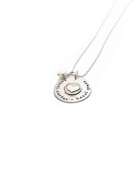 A sterling silver disc with hand stamped names. Layered with a gold-filled disc and a sterling silver heart in the middle.