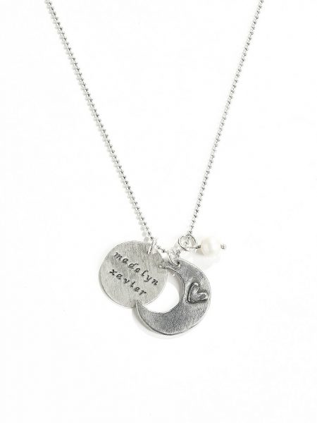"A moon charm hand stamped with ""I love you to the moon and back"" on one side and a heart on the other. Personalize necklace with names on the disc"