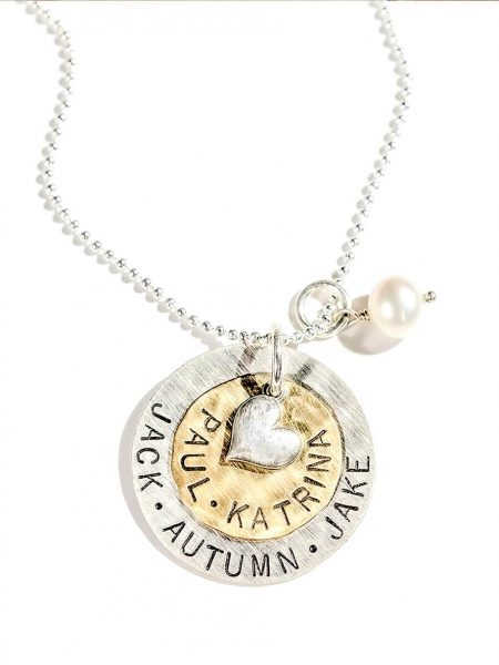A large sterling silver disc layered with a brass disc and topped with a silver heart. Hand stamped jewelry gift for mom, grandma