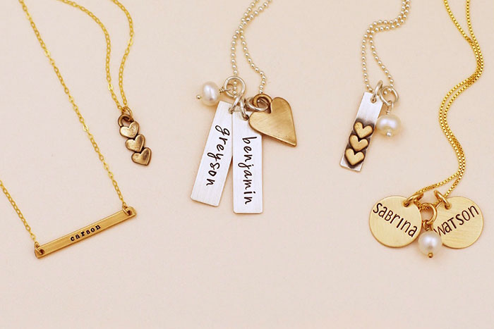 Displaying Sterling Silver and Gold Jewelry pieces personalized with names, initials, heart charms, pearls.