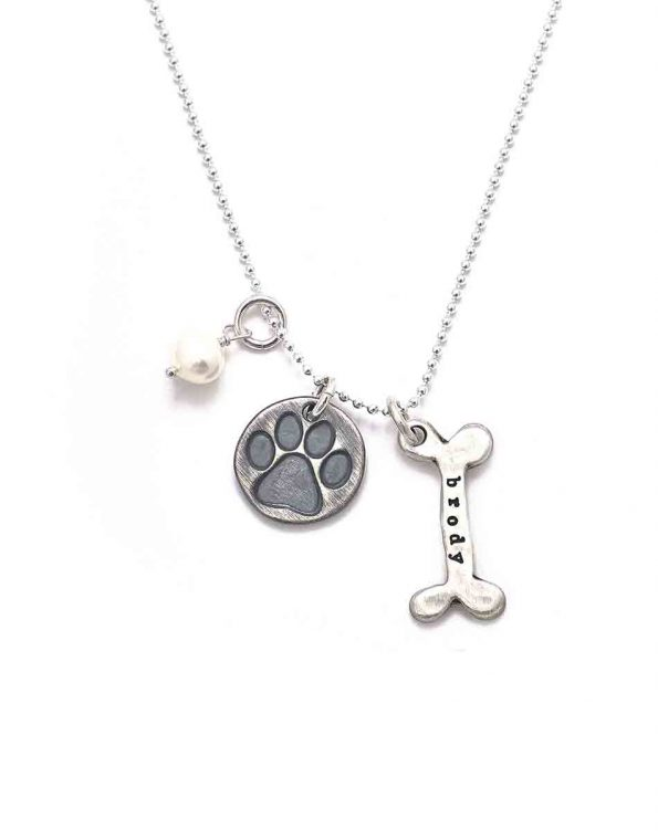 Best gift for dog lovers. A paw print sterling silver disc along with a hand formed bone with pup's name hand stamped