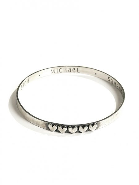 Sterling silver bangle hand stamped on the inside with names or a secret message. Add hearts on the outside for each name.
