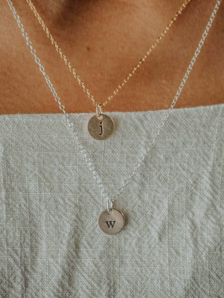 Hand-stamped initial on a tiny disc. Available in sterling silver or gold. Great personalized jewelry for wife, mom, new mom