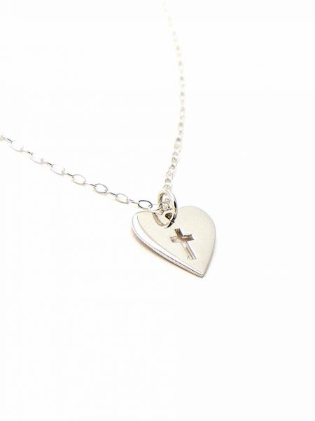 A sterling silver heart charm with a lovely cross cut out in the middle of it, hung on a sterling dainty chain. Perfect for girls of any age