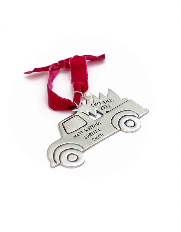 A pick-up truck and a Christmas tree hand-molded and cast in fine pewter with hand-stamped family's names hung on a red velvet ribbon along with a freshwater pearl.